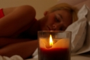 Woman asleep with lit candle
